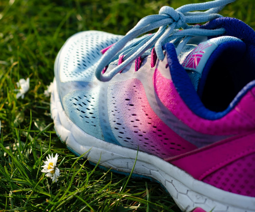 A pink and blue running shoe on grass