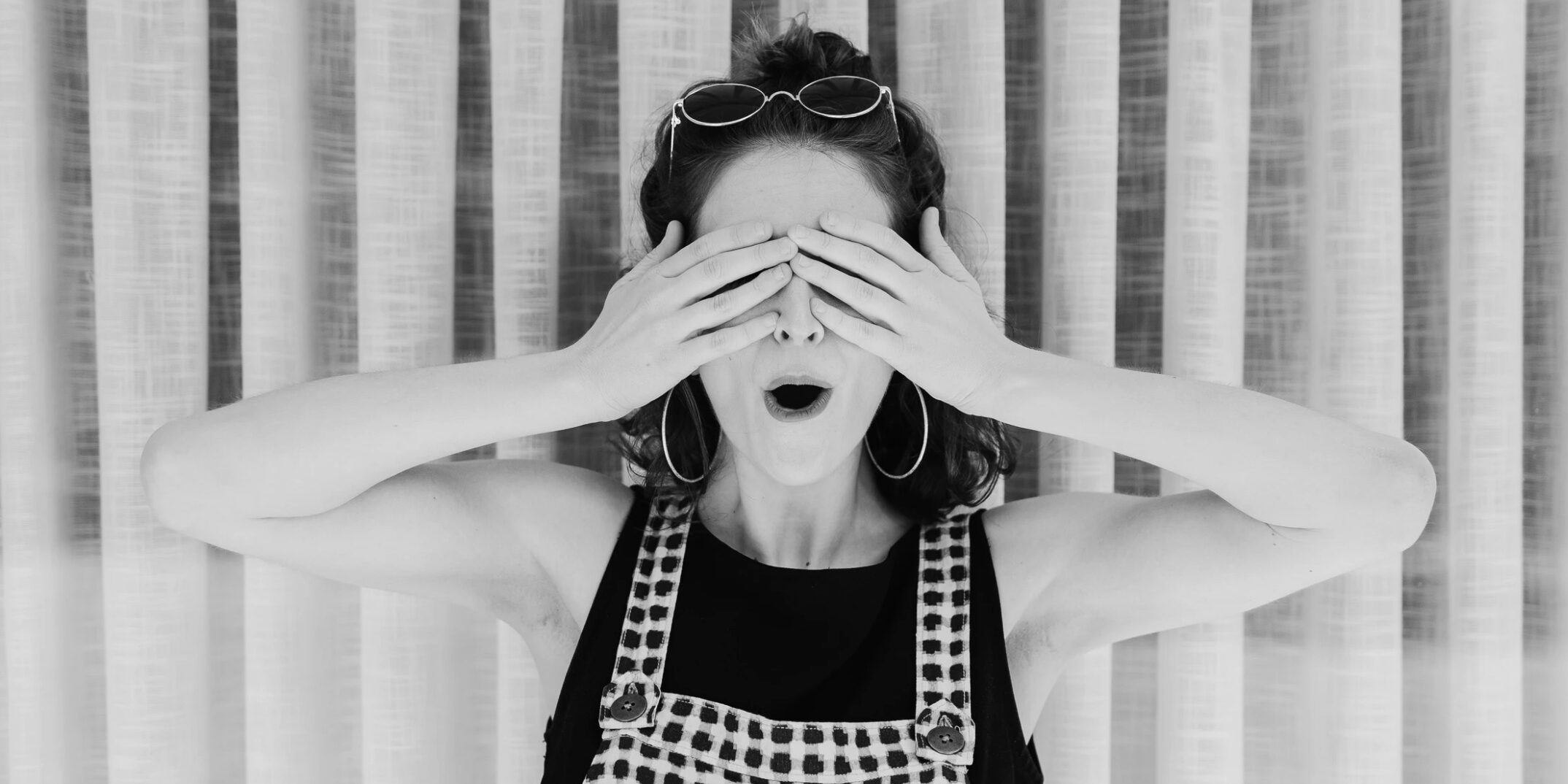 Young woman covering her eyes in embarrassment